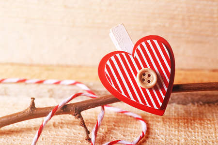 Valentine concept. Red heart with tree branch on wooden background