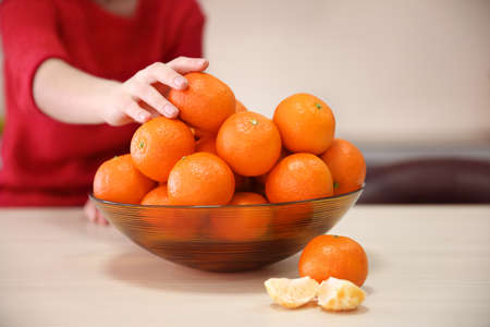 Woman taking tangerine from the bowl