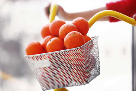 Woman driving a bicycle with tangerines in basket