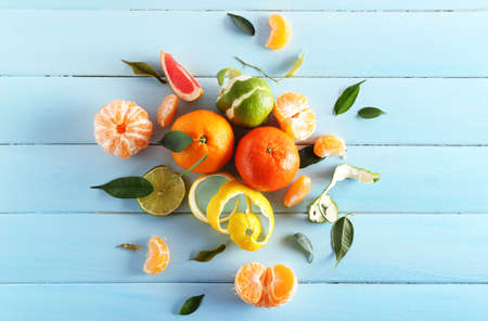 Fresh citrus fruits with green leaves on wooden background