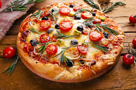 Delicious fresh pizza on wooden table closeup Stock Photo