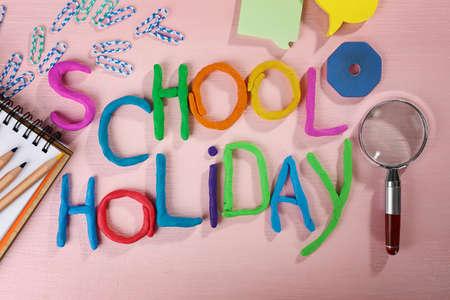 Napis SCHOOL HOLIDAY wykonany z kolorowej plasteliny i materiałów piśmiennych na kartkach papieru w tle