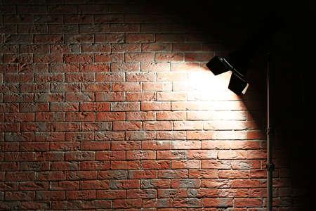 Studio light flash on brick wall background Stock Photo