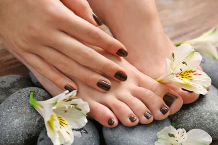 Pieds féminins manucurés et main avec des fleurs sur les pierres du spa closeup