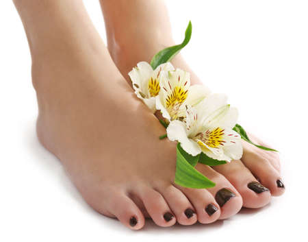 Manicured female feet with flowers isolated on white