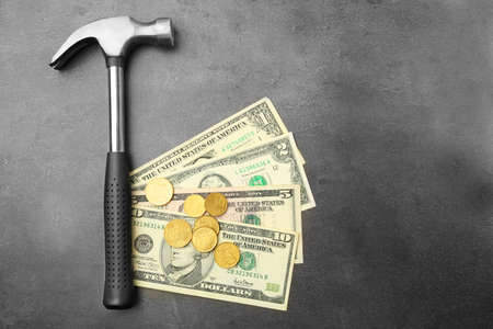 Money with hammer on grey background, close up