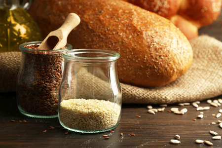 Sesame and flax seeds in banks with bread on wooden table background, closeup Stock Photo