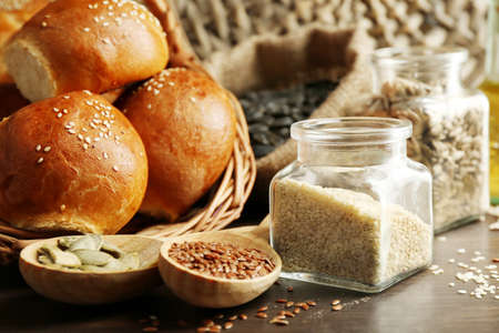Composition of seeds and buns on wooden table background, closeup