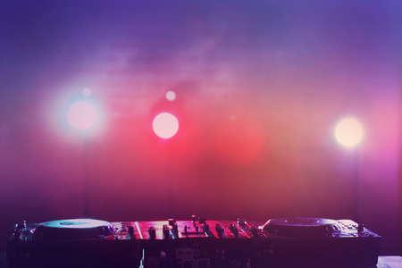 DJ mixer against bright lights background