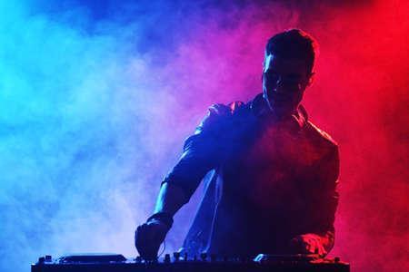 DJ playing music at mixer on colorful foggy background Banque d'images