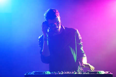 DJ playing music at mixer on colorful foggy background 版權商用圖片