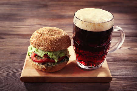 Glass mug of dark beer with hamburger on wooden table, close up Stock Photo