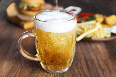 Glass mug of draft light beer with snacks on dark wooden table, close up