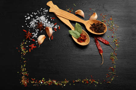 Different spices and spoons on wooden table