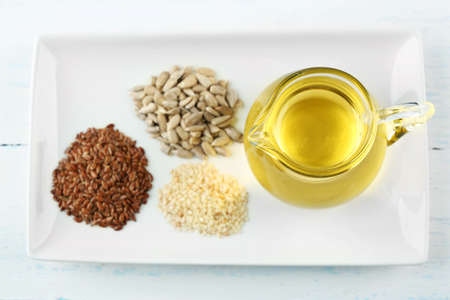 Different kinds of seeds and oil on wooden table Stock Photo