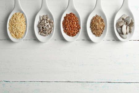 Diferentes tipos de semillas en cucharas en la mesa de madera