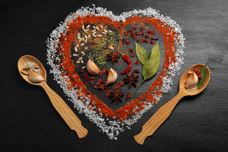 Spices on table in shape of heart on wooden table