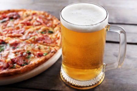 Tasty pizza and glass of beer are on wooden table, close up