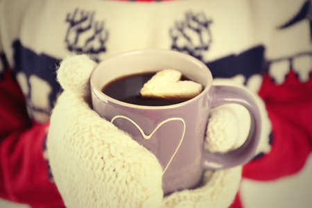Female hands in warm mittens holding cup of hot coffee with heart marshmallow, close up