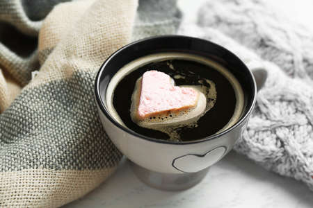 Cup of hot coffee with heart marshmallow and warm scarfs on light wooden background, close up