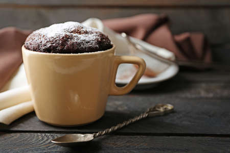 Chocolate fondant cake in cup on wooden table closeup Stock Photo