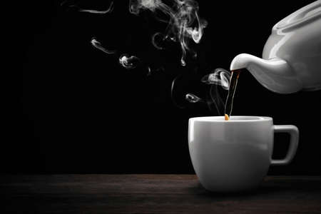 Pouring hot tea from a kettle into a cup on black background, close up