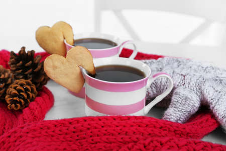 Heart shape cookie on cup of coffee with red knitted scarf closeup Reklamní fotografie
