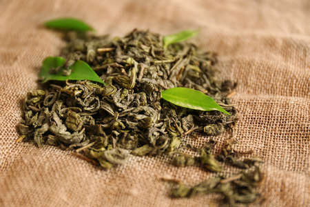 Granulated tea with green leaves on sackcloth background Imagens