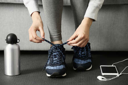 Woman tying up running shoes