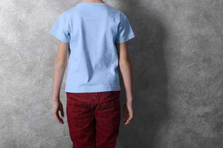 Clothes advertising. Boy in T-shirt and red trousers against grey textured wall background, back view
