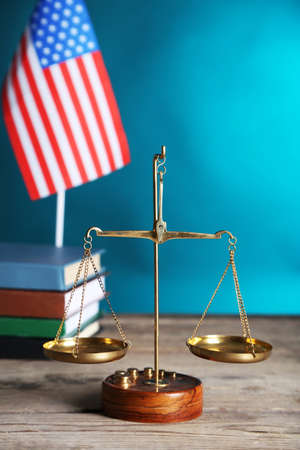 Justice scales with USA flag and books  on blue background Stock Photo