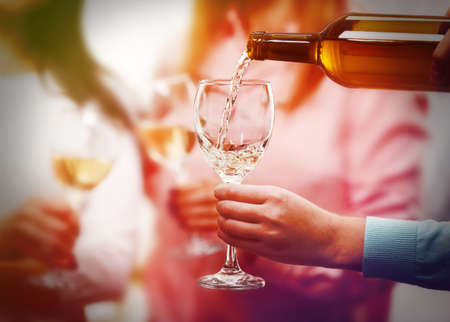 Pouring white wine into glass at hen-party, close up Stockfoto