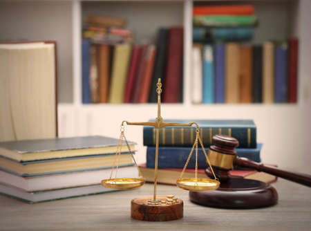 Justice scales with gavel and stack of books on wooden table Stock Photo