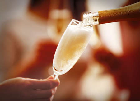 Pouring champagne into glass at hen-party, close up