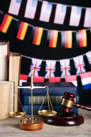 Wooden gavel with justice scales, books and national flags on black background Stock Photo