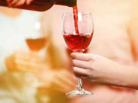 Pouring red wine into glass at hen-party, close up Stock Photo