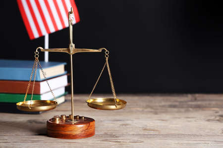 Justice scales with USA flag and books on black background
