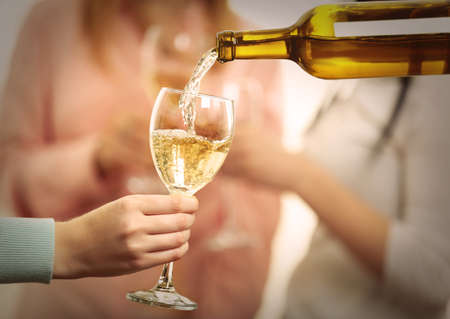 Pouring white wine into glass at hen-party, close up Stock Photo