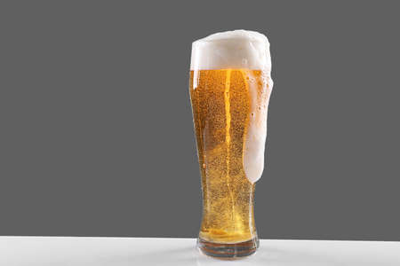 Glass of lager beer with thick froth on grey background 스톡 콘텐츠
