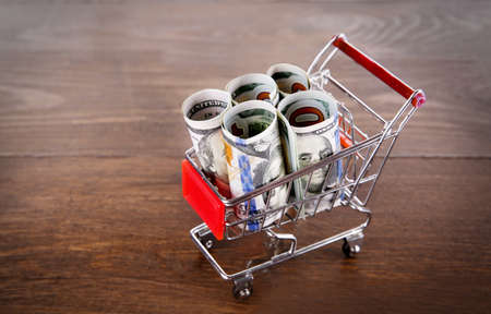 Small shopping trolley with dollars banknotes on wooden background Stock Photo