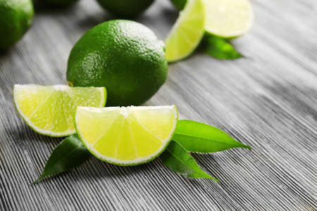 Limes and slices on wooden table, closeup Stock Photo