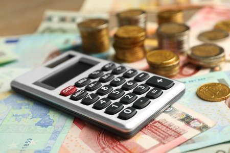 Money concept. Grey calculator with banknotes and coins, close up