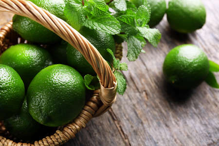 Limes with mint in wicker basket Stock Photo