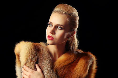 Beautiful young woman with luxury fur on dark background  Stockfoto