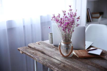 Modernes Interieur. Bequemer Arbeitsplatz. Holztisch mit schönem Blumenstrauß von Blumen und von Laptop auf ihm, Abschluss oben Standard-Bild