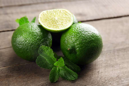 Limes with mint on wooden table Stock Photo
