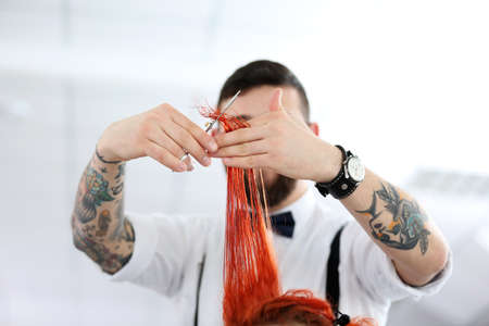 Hairdresser cutting red curls