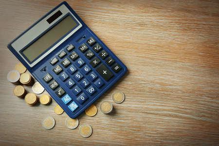 Money concept. Black calculator with coins on wooden table Banco de Imagens - 95580872