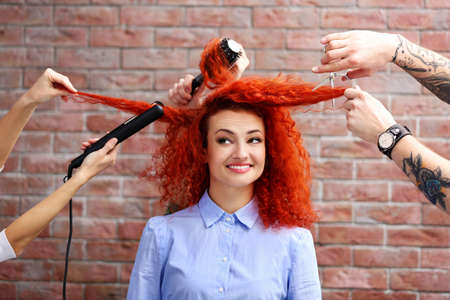 Red haired beautiful girl with many hands and accessories Stock Photo
