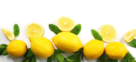 Colorful yellow lemons sliced and halved with mint sprigs isolated on a white background, top view